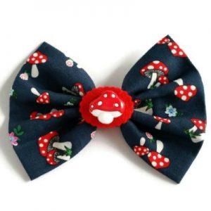 handgemaakte donkerblauwe strik met paddelstoeltjes en bloemetjes en rood vilten medallion met paddenstoek