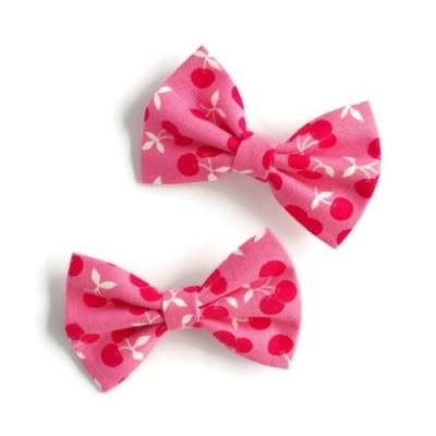 setje van twee handgemaakte kleine haarstrikjes van roze stof met kleine rode kersjes
